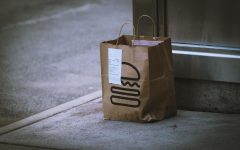 Photo by Jon Tyson on Unsplash. A food delivery sits on a doorstep.