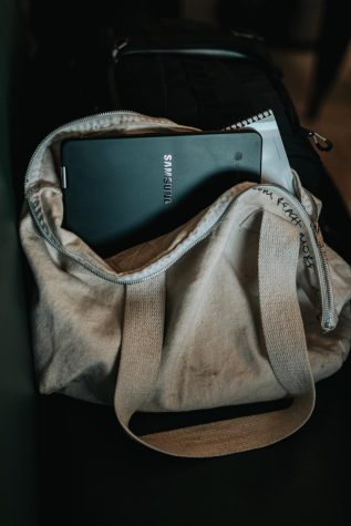 Photo by Nathan Dumlao on Unsplash. A device sits in a students backpack.